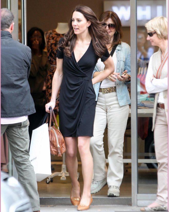 foto de Kate Middleton usando um vestido preto simples de decote em V com cabelos soltos saindo de uma escola. Ela usa bolsa e sapatos cor caramelo.