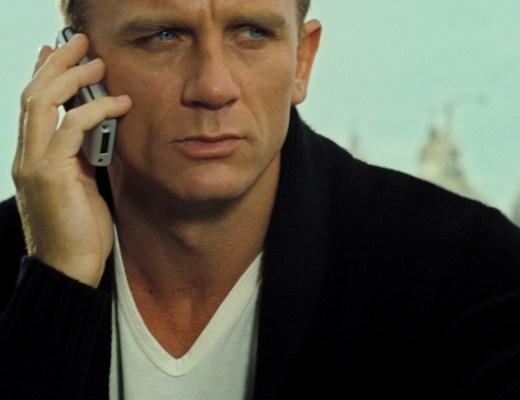 """Ator em foto do tronco , frontal, usando uma camiseta com decote """"V"""" na cor branca. Ele segura o celular junto a orelha direita. Sobre a camiseta ele veste um casaco na cor preta."""