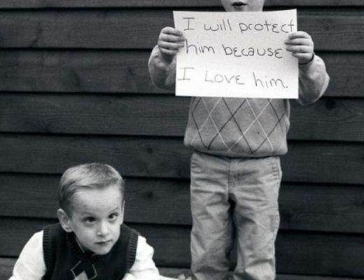 Foto em preto e branco, com jeito de antiga. Mostra um menino de 6 anos em pé, segurando uma placa com os dizeres: I will protect him because I love him. Sentado no chão, outro menino, um pouco mais velho.