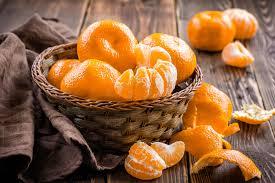 Uma cesta cheia de tangerina e ao lado sobre a mesa, uma tangerina aberta em gomos.