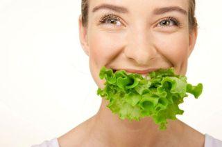 Uma mulher linda, em foto frontal do rosto, tem em sua boca uma enorme folha de alface comum. Ela sorri , pela situação.