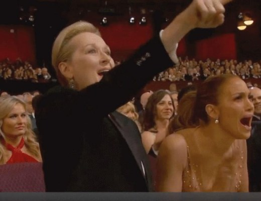 Imagem do auditório da entrega do Prêmio Oscar 2015. Em primeiro plano estão Maryl Streep e Jennifer Lopez, atrizes, aplaudindo efusivamente.