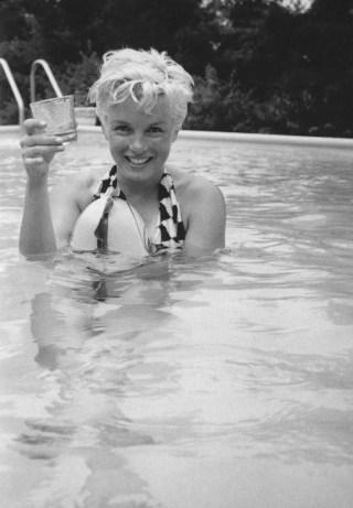 Imagem em preto e branco, Atriz Marilyn Monroe, com um maiô, está dentro de uma piscina, mas na sua mão direita tem um copo de vidro.