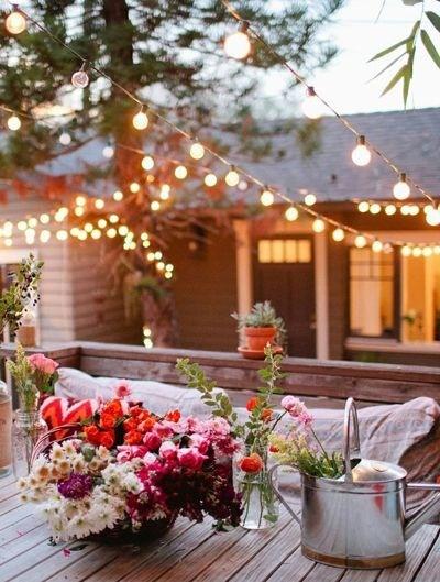 Imagem de casa no campo, num dia lindo, em frene a ela um ciprestre. No jardim uma mesa florida, com um regador servindo de vaso e com flores. No ar muitos fios com lâmpadas acesas.