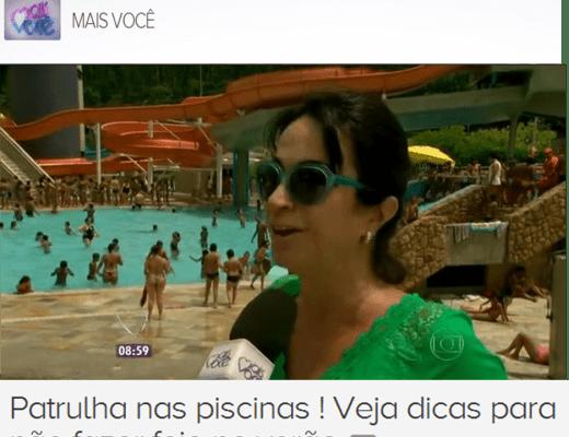 Claudia Matarazzo numa reportagem para o Programa Mais Voce da Rede Globo, está na borda de uma piscina popular, usando uma saia de praia verde e óculos escuros, atrás na imagem uma piscina lotada com milhares de pessoas.
