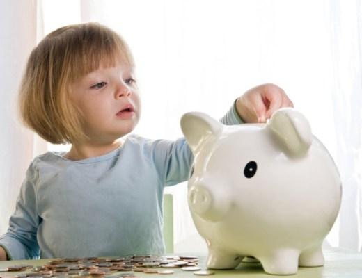 menina de 2 anos, com olhos claros e cabelo loiro curtinho de franjinha, colocando moedas em um cofrinho em forma de porco.