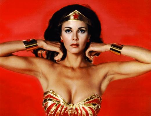 a foto mostra a atriz que interpretou a heroina Mulher Maravilha. Ela tem cabelos pretos, na altura do ombro e usa uma faixa dourada com uma estrela vermelha. Seus braceletes e corpete também são vermelhos e dourados.