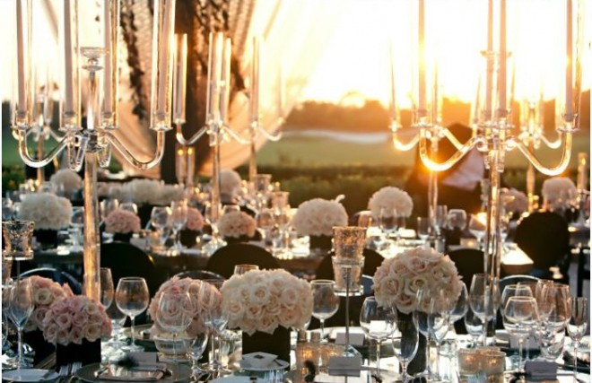 Uma mesa com candelabros de cinco braços em prata e muitos vasos baixos de rosas brancas está colocada a frente de uma janela. Através dela se vê a luz de por do sol que acentua a beleza da pradaria de das taças de cristal colocadas nos lugares dessa mesa formal de casamento. A imagem é de requinte e aconchego enfatizada pelo luz quente de final de tarde.