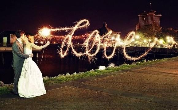 """Um casal de noivos a beira de um lago se beija e ao fundo ve-se um castelo, e, em primeiro plano, a palavra """"Love""""escrita com fogos de artifício e em letra cursiva e rococó."""