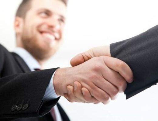 a foto mostra dois homens de terno apertando as mãos.