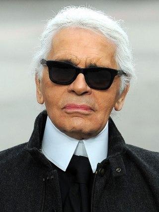 Karl Lagerfeld, estilista famoso, sempre com seus cabelos grisalhos, óculos escuros, em foto do rosto, usa camisa branca com golas altas e veste casaco cinza escuro.