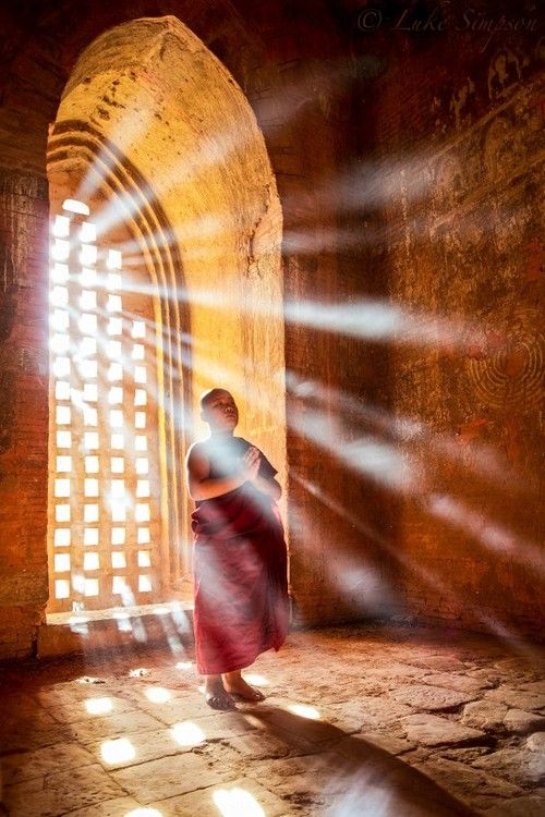 monge budista tibetano, vestindo seus mantos sagrados na cor marsala, está de pé com as mãos unidas junto ao peito junto a uma ampla janela do tempo por onde entra uma grande luz.