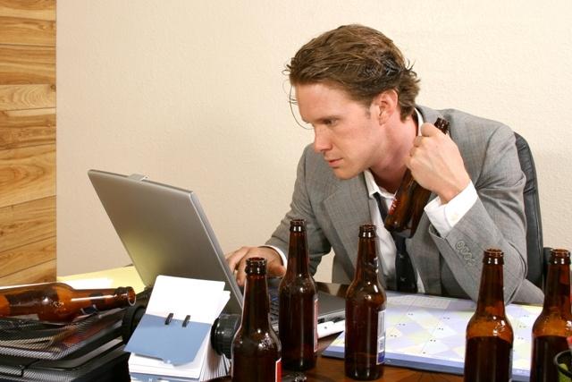 Imagem de um homem usando terno cinza e gravata com o laço solto, está sentado numa mesa de escritório, usando o seu notebook e a sua frente , sobre a mesa temos seis garrafas de cervejas vazias e ele segura mais uma garrafa em sua mão esquerda. Ele olha atentamente para a tela do notebook.