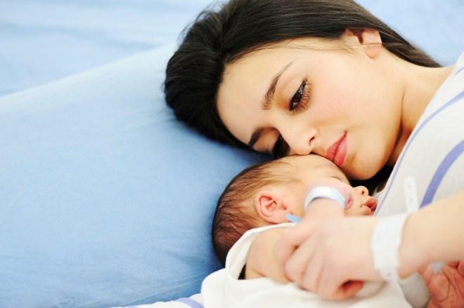 mãe jovem, deitada numa cama com lençóis azuis , abraçada ao seu bebê que dorme profundamente.