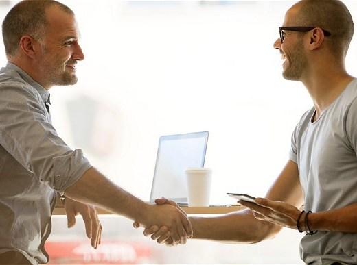 Um homem usando camisa social , com as mangas dobradas, cumprimento outro homem, de óculos, que usa camiseta , decote careca, de cor cinza, que tem na sua mão esquerda um mini tablet.