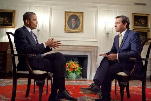No Gabinete do Presidente, na Casa Branca, nos EUA, o Presidente Barack Obama está sentado em frente a um jornalista, que está realizando uma entrevista. Ambos estão de terno escuro, camisa na cor branca e o Presidente está com uma gravata azul acinzentada e o jornalista com a gravata cor amarela.
