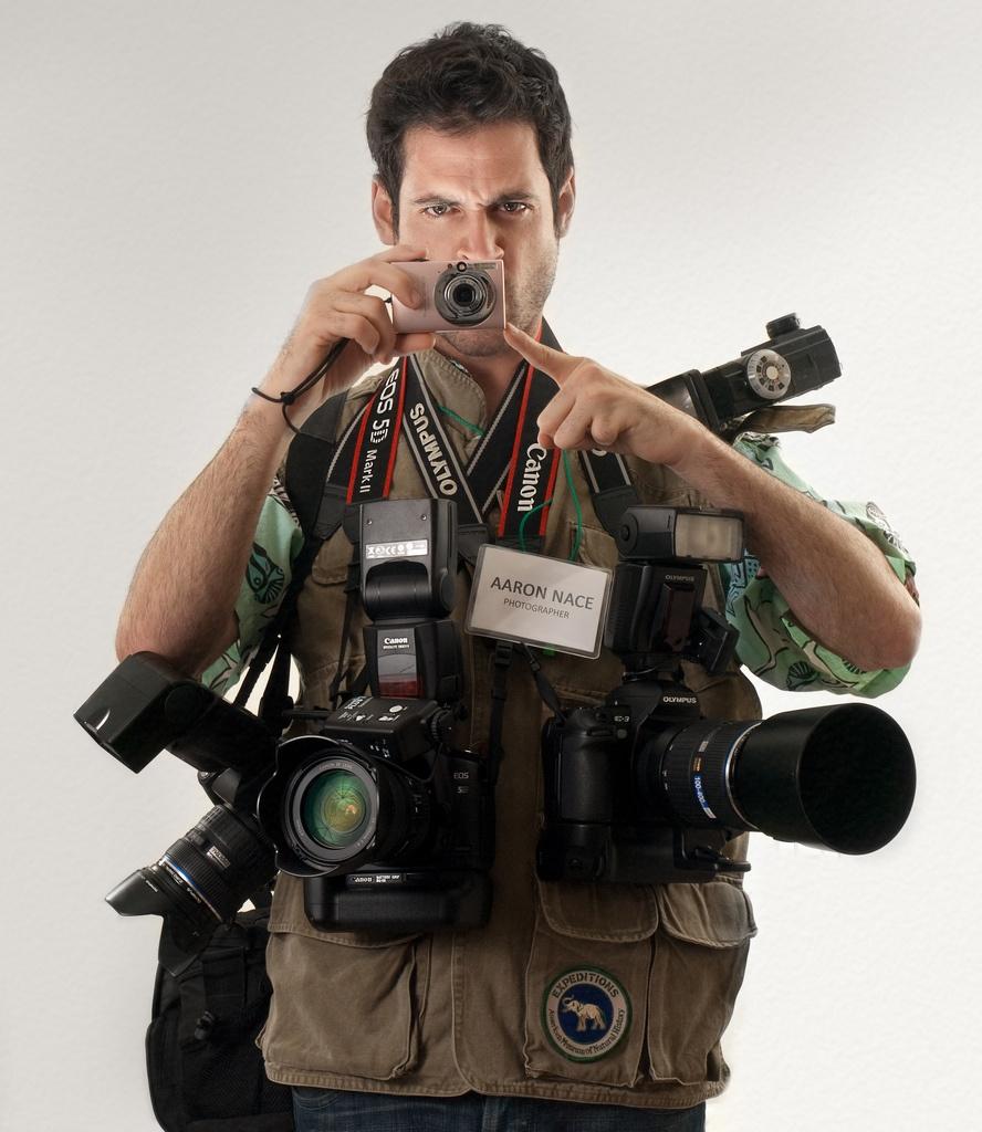 Fotógrafo num imagem frontal , ele alto, cabelos na cor marrom escuro, em sobre o corpo inúmeras câmeras fotográficas de vários tamanhos e lentes de vários tipos.