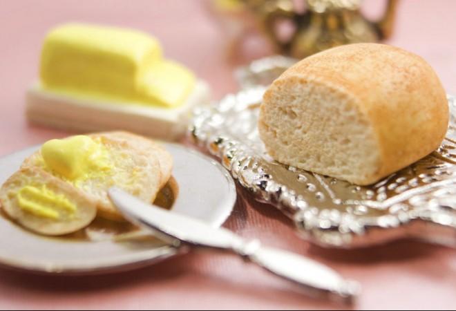 Uma faca sobre um pedaço de pão, que está num pratinho