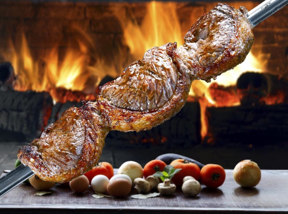 Um espeto com 3 peças de picanha, inclinado com a ponta apoiada na mesa, ao fundo a chama ardente da churrasqueira e sobre a mesa, tomates, cebolas pimentões e alho. decoram o ambiente