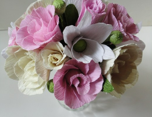 Várias rosas e lisianthios em três cores suaves: cor de rosa claro, creme e branco estão amarrados formando um buquê redondo e harmonioso.