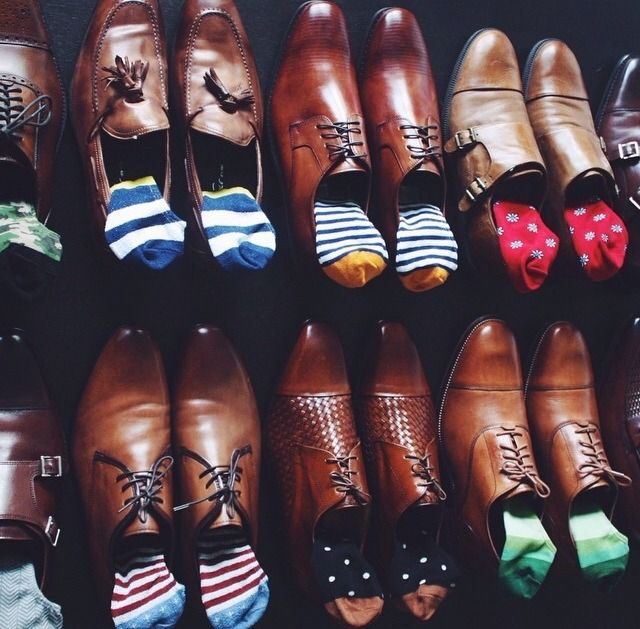 sapatos em tons marrons, tendo cada um com um tipo de meia colorida. algumas listradas em tons azuis, outras vermelhas, outra com bolinhas brancas no fundo azul.