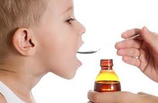 a foto mostra um menino loirinho de 5 anos de perfil, abrindo a boca para tomar remedio.