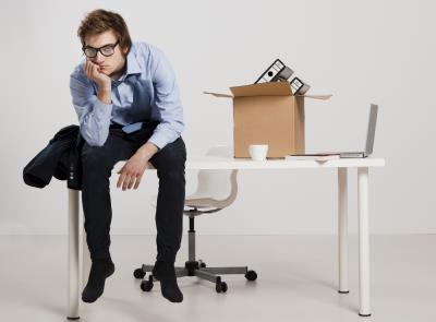 Homem usando óculos está sentado numa mesa ao lado de uma caixa de papelão com pastas. Ele usa calça escura, camisa social, azul e a gravata está torta. A expressão é que ele está deprimido.