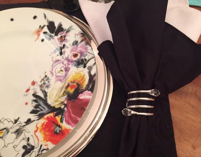 Um prato branco, raso mostra estampa floral desenhada livremente. Flores de campo em cor de vinho, vermelho coral, preto e amarelo - em um buquê campestre estilizado que ocupa apenas um terço da circunferência do prato. Ele esta sobre um souplat de prata e um jogo americano preto com guardanapo tambem preto seguro por um porta guardanapos prateado em espiral arrematado por um cristal lapidado. A idéia é de uma mesa alegre e moderna - proporcionada principalmente pelo toque de preto.