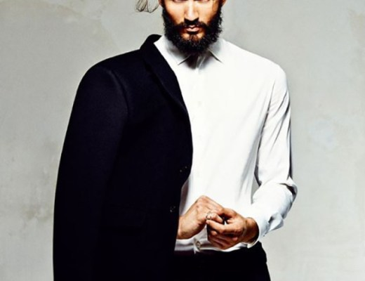 Um homem de frente, usando calça cor preta, camisa social, cor branca, com mangas cumpridas. Tem sobre o ombro direito o paletó. Ele usa barba e bigode e cabelos presos em coque no alto da cabeça.