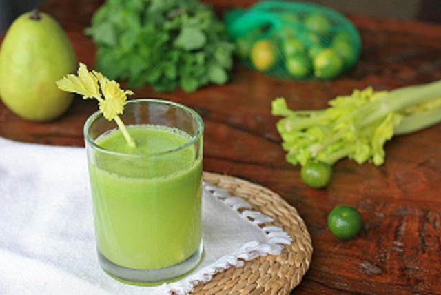 um copo de suco verde e cremoso sobre uma toalhinha branca que por sua vez está sobre uma mesa de madeira rústica com folhas de cheiro verde ao fundo.