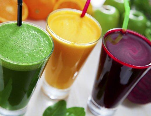 Tres copos grandes de vidro, em cada um deles contem um suco detox de uma fruta. O da esquerda cor verde, no centro, suco cor amarela, e da direita, suco da cor roxa. dentro deles contem um canudo.
