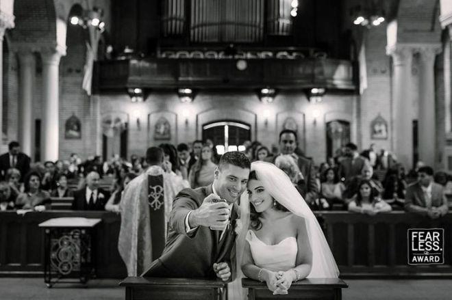 foto do interior de uma igreja em preto e branco, onde o noivo no altar, faz uma selfie com a noiva.