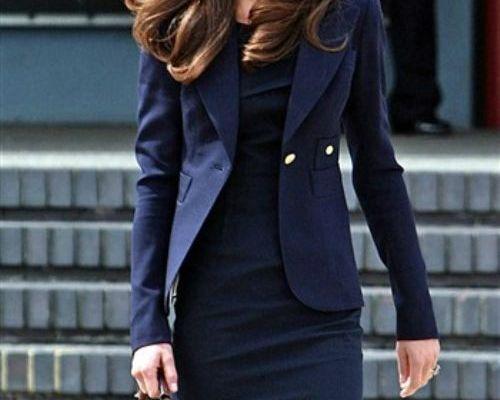 Kate Middleton em imagem recente com um vestido e paletó curto azul marinho forte. Ela está de cabelos soltos e usa uma bolsa preta com cabo de bambu.