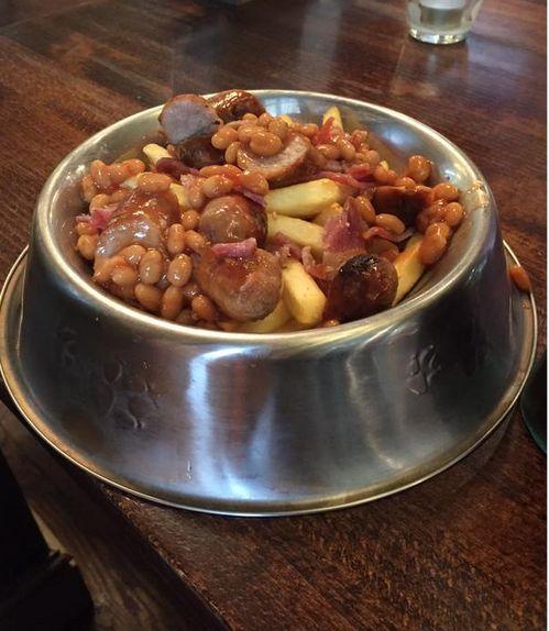 Uma vasilha redonda e funda de alumínio própria para alimentos de cachorros e gatos apresenta uma feijoada com batatas fritas e pedaços de paio e linguiça
