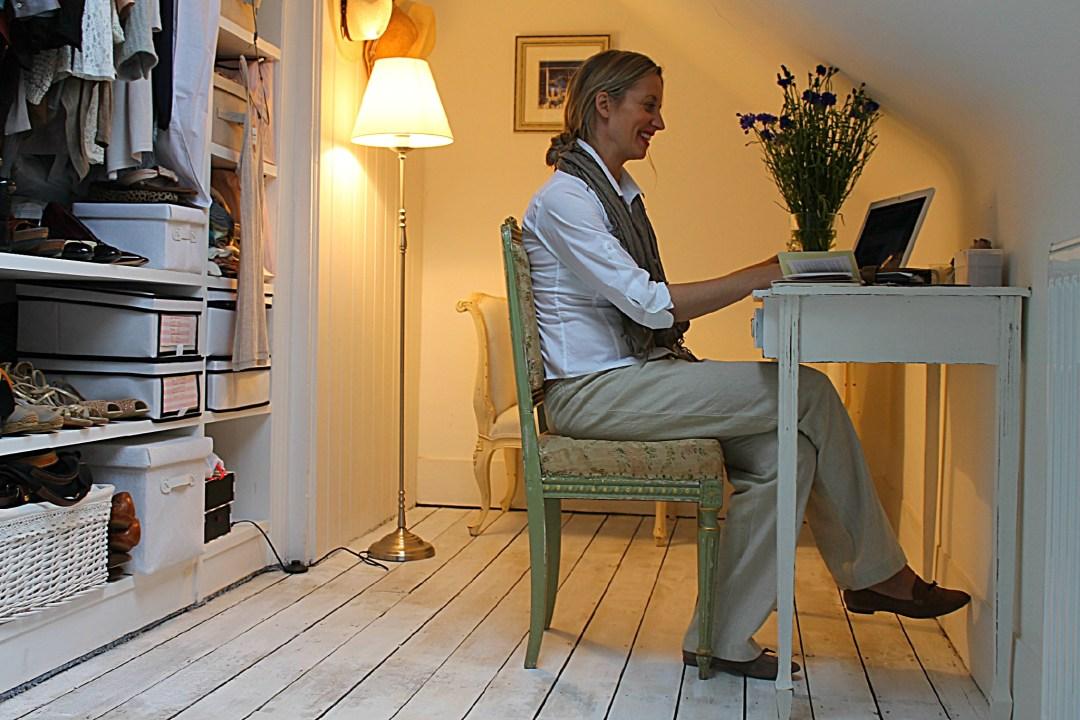 Num quarto , a esquerda um armário, com roupas , sapatos, a direita, uma mulher loira, está sentada diante de uma mesa. Ela usa o notebook. Ao fundo uma luminária acesa dá um ar de beleza ao ambiente.