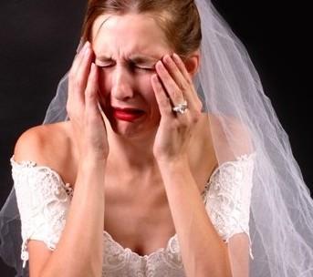 mulher usando vestido de noiva , com véu e grinalda, chora e está com as mãos no rosto em cena de desespero.