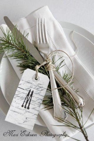 talheres sobre um prato, cor branca. Eles estão amarrados com barbante junto ao ramo de alecrim e uma taget com a letra M.