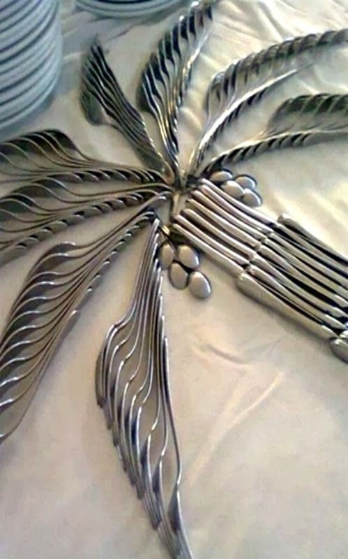 Sobre uma mesa de buffet, Arranjo de talheres em forma de palmeira, o tronco formado por facas arranjadas e as folhas feitas com garfos arranjados.
