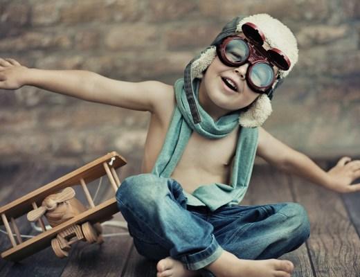 Criança de 6 anos, sentada no chão, sem camisa e de bermuda, cor azul, e lenço azul no pescoço, usa óculos de piloto e boné. está com os braços esticados ao lado do corpo, como tivesse plainando. Ao seu lado um pequeno avião de madeira.
