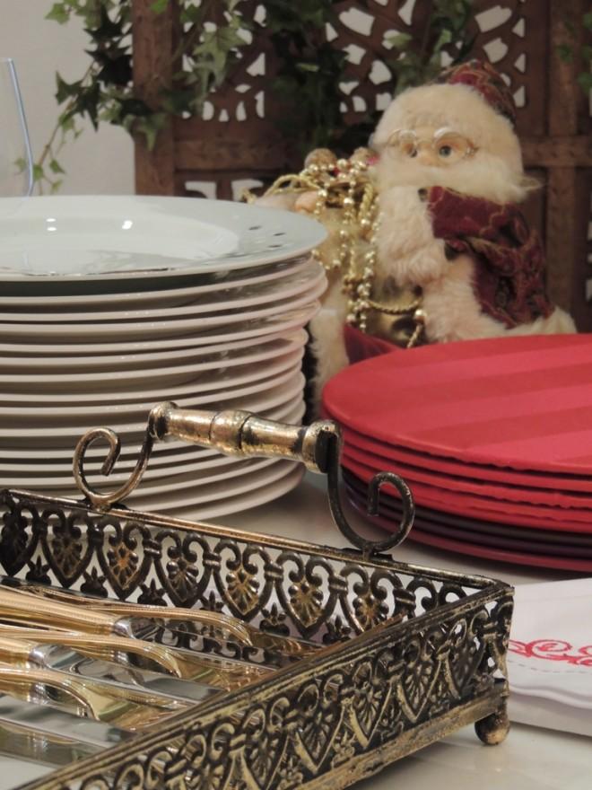 sobre uma mesa estão colocados vários elementos para servir um jantar: uma pilha de pratos ao fundo, apoios de pratos vermelhos no plano médio e na frente, uma bandeja espelhada está com facas e garfos dispostos para facilitar o manuseio na hora de pegar.