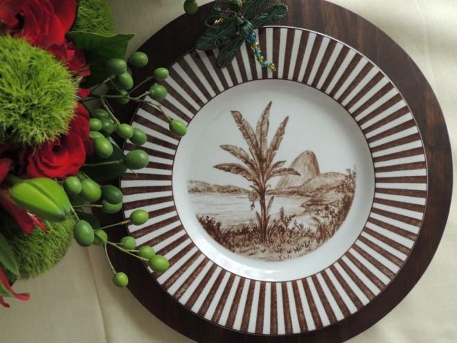 sobre um souplat de madeira um prato raso estampado com uma palmeira brasileira e o corcovado ao fundo em cor sépia. A borda do prato é toda listrada em marrom e branco criando um efeito moderno emoldurando a paisagem antiga.