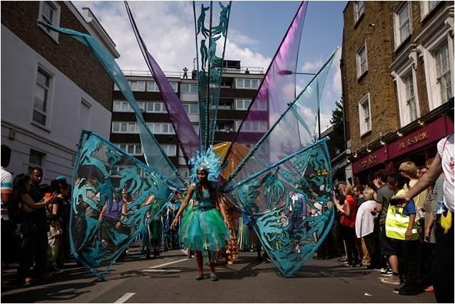 bloco carnavalesco na rua, ao centro uma mulher usando fantasia verde transparente tem em suas costas mastros com bandeiras coloridas. ao redor muitas pessoas apreciam o desfile.