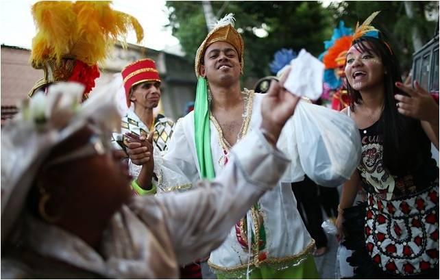 foliões de bloco de rua, vestidos de piratas e alguns foliões brincam na avenida, muitas plumas e adereços coloridos.