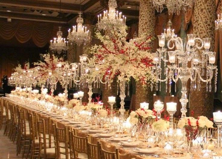mesa de banquete, completa com porcelanas e prataria, ainda com vasos altos de flores e inúmeros castiçais complementam a decoração