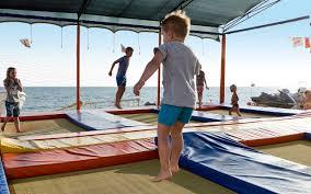 Playground a beira mar, onde várias crianças pulam sobre colchões coloridos, em cores vermelho e outros azuis.