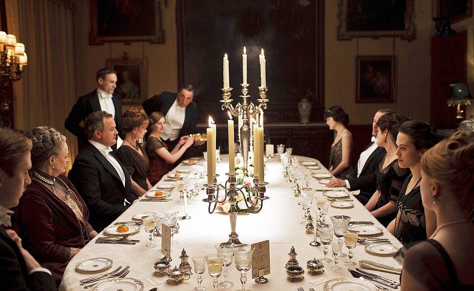 mesa clássica de uma família inglesa - do seriado Downton Abbey - os homens usando casacas pretas e as mulheres usando vestidos longos. Ao centro dois candelabros de cinco velas acesas.