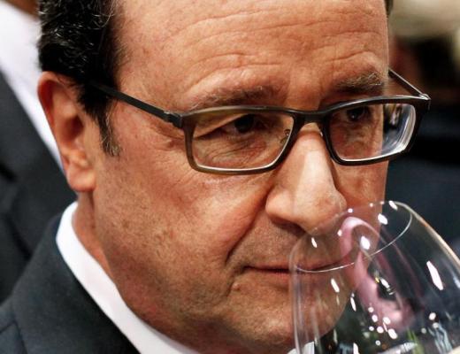 Presidente François Hollande em meio a outras pessoas de terno, ele segura uma taça de vinho junto ao seu nariz,