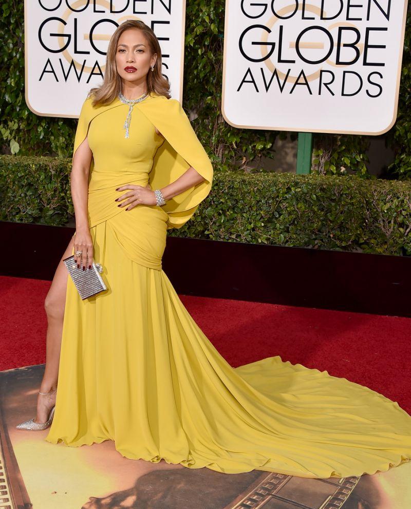 A atriz Jennifer Lopez usa vestido longo, cor amarelo ovo, com um tipo de mini capa sobreposta da mesma cor. Os seus cabelos estão clareados quase loiro, cor de batom vermelho e ela usa uma bolsa em prata.