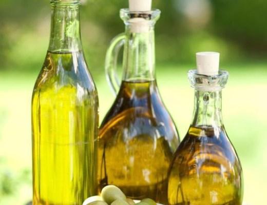 três garrafas com azeite de oliva, a primeira a esquerda, tipo garrafa de vinho transparente com rolha, a do meio estilo garrafa de conhaque transparente e a ultima é um pequeno garrafa transparente. a frente um pote com azeitonas verdes.