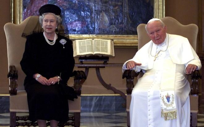 Em audiência papal no Vaticano. Rainha Elizabeth II usa vestido cor preta, está sentada a esquerda , ao centro um biblia aberta sobre uma mesa e a direita o Papa João Paulo II, sentado usando o seu traje tradicional todo branco.